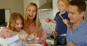 Eltern, die ihre Tochter unterrichten, das Ei beim Backen von 4k zu brechen stock footage