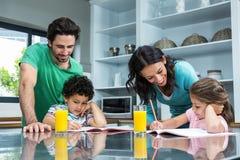 Eltern, die ihren Kindern tun Hausarbeit helfen Lizenzfreies Stockbild