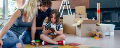 Eltern, die ihren kleinen Sohn überwachen, Tablette zu spielen stockfotografie