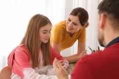 Eltern, die ihrer Jugendlichtochter mit Hausarbeit helfen stockbild