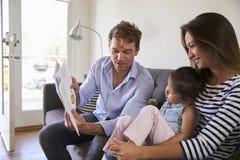 Eltern, die mit Baby-Tochter auf Sofa At Home lesen stockfotos