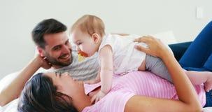 Eltern, die mit ihrem Baby im Schlafzimmer spielen stock video