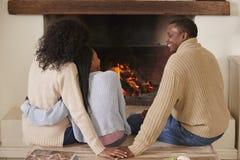 Eltern, die mit Tochter im Aufenthaltsraum nahe bei offenem Feuer sitzen lizenzfreies stockbild