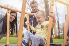 Eltern, die Spaß mit ihrem Kind im Parkspielplatz haben stockbilder