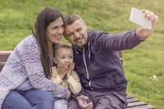 Eltern, die Spaß mit ihrem Kind im Parkspielplatz haben stockfotografie