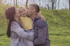 Eltern, die Spaß mit ihrem Kind im Parkspielplatz haben lizenzfreies stockfoto