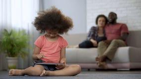 Eltern, die stolz wie ihre Tochter arbeitet an Tablette, Wunderkind beobachten stockbild