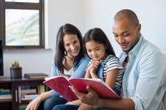 Eltern, die Tochterübungsbuch schauen lizenzfreies stockbild