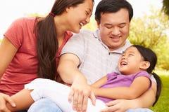 Eltern, die Tochter im Park streicheln stockbild