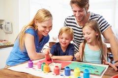 Eltern, die zu Hause Bild mit Kindern malen Stockbilder