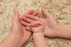 Eltern halten die Kinderhand Stockbilder