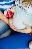 Eltern halten Hände auf Bauch der schwangeren Mutter Lizenzfreie Stockfotos