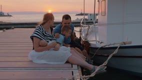 Eltern mit älterem Sohn und dem Baby, die auf dem Pier bei Sonnenuntergang sitzt stock video