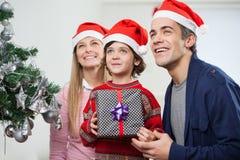 Eltern mit dem Jungen, der Weihnachtsgeschenk hält lizenzfreie stockfotografie