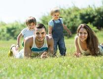 Eltern mit den Kindern, die in das Gras legen Stockfotografie