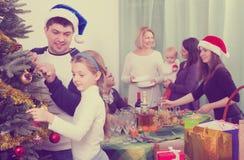 Eltern mit den Kindern, die für Weihnachten sich vorbereiten stockfotografie