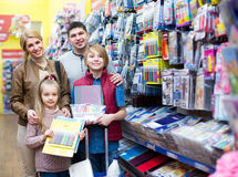 Eltern mit den Kindern, die Schreibmaterialien kaufen Stockfotografie