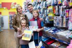 Eltern mit den Kindern, die Schreibmaterialien vorwählen Stockfotos