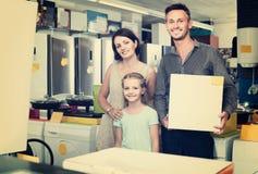 Eltern mit der Tochter, die großen Kasten mit neuer Elektronik in ho hält stockbild