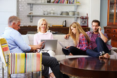 Eltern mit erwachsener Nachkommenschaft unter Verwendung Digital-Geräte zu Hause stockfotografie
