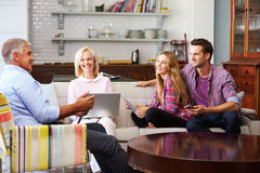Eltern mit erwachsener Nachkommenschaft unter Verwendung Digital-Geräte zu Hause lizenzfreie stockfotos