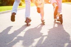 Eltern mit Kinderreitrollern im Sommer Lizenzfreie Stockfotografie