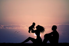 Eltern mit Sohn bei Sonnenuntergang Stockfotografie