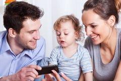 Eltern mit Sohnbetrachtungsfotos Stockbilder