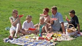Eltern mit vier Kindern, die Wassermelone genießen stock video footage