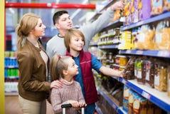 Eltern mit zwei Kindern, die knusperige Flocken im Shop wählen lizenzfreie stockfotografie