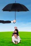Eltern und ihr Kind, die auf Gras unter Regenschirm liegen Lizenzfreies Stockbild