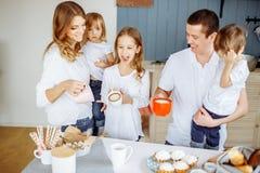 Eltern und ihre drei Kinder, die in der Küche essen und zusammen genießen stockfotografie