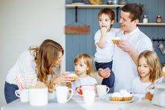 Eltern und ihre drei Kinder, die in der Küche essen und zusammen genießen lizenzfreie stockbilder