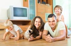 Eltern und Kinder, die auf dem Boden lachen Lizenzfreie Stockfotografie