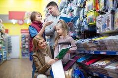 Eltern und Kinder, die Schreibmaterialien kaufen Stockbild
