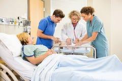 Eltern und Krankenschwester Doktor-Examining Baby While Stockfotos