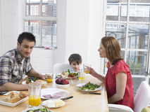 Eltern und Sohn, die Mahlzeit an Speisetische haben Stockfoto