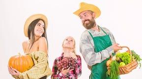 Eltern und Tochterlandwirte feiern Erntefeiertag Lokalisiertes Wei? des Familienlandwirtg?rtner-Korbes Ernte stockfotos