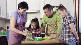 Eltern unterrichten ihre Kinder, eine von ihnen mit Down-Syndrom, ihr eigenes Mittagessen vorzubereiten stock footage