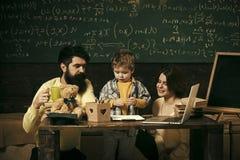 Eltern unterrichtet Sohn, Tafel auf Hintergrund Junge, der auf Mutter und Vati mit Aufmerksamkeit hört Familiensorgfalt über Bild lizenzfreie stockfotos