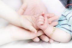 Eltern, welche die Hand des Babys schleppen Stockfotos