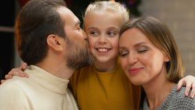 Eltern, welche die Tochter, Kamera betrachtend, glückliche Familie am Weihnachtsfeiertag küssen stock video footage