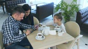 Eltern, welche die Zeit betrachtet Tablette verbringen, während ihre Tochter ihre Aufmerksamkeit im Café erregen möchten stock video