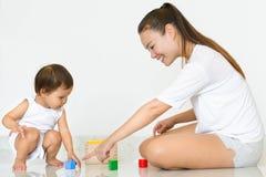 Elternteil benutzt Bausteine, um Kleinkindformen und -farben zu unterrichten Stockfotografie