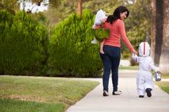 Elternteil, das Kindern Trick nimmt oder bei Halloween behandelt stockfotos