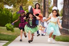 Elternteil, das Kindern Trick nimmt oder bei Halloween behandelt lizenzfreie stockfotos