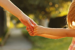 Elternteil hält die Hand eines kleinen Kindes Stockbild