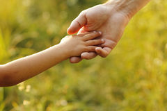 Elternteil hält die Hand eines kleinen Kindes Stockfotografie