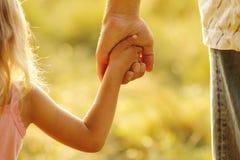 Elternteil hält die Hand eines kleinen Kindes lizenzfreies stockfoto