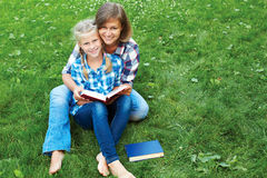Elternteil- und Kinderlesebücher zusammen im Park Stockfoto